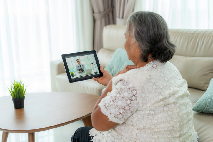 elderly woman on a video call with doctor