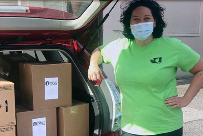 masked woman standing by trunk with donations