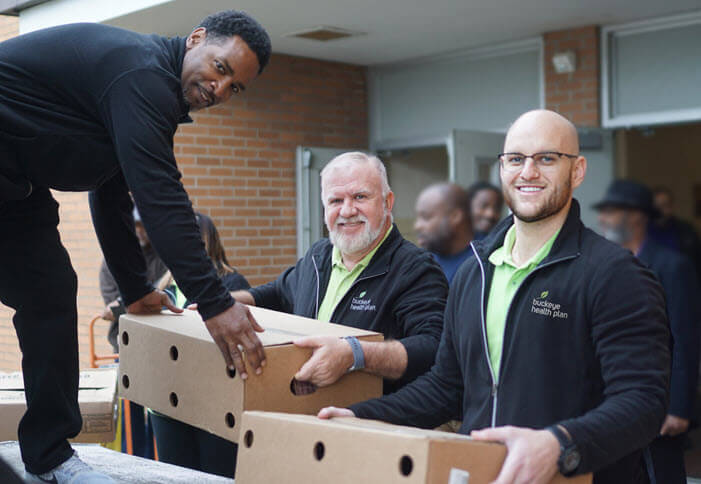 Centene employees load boxes of food on a pallet