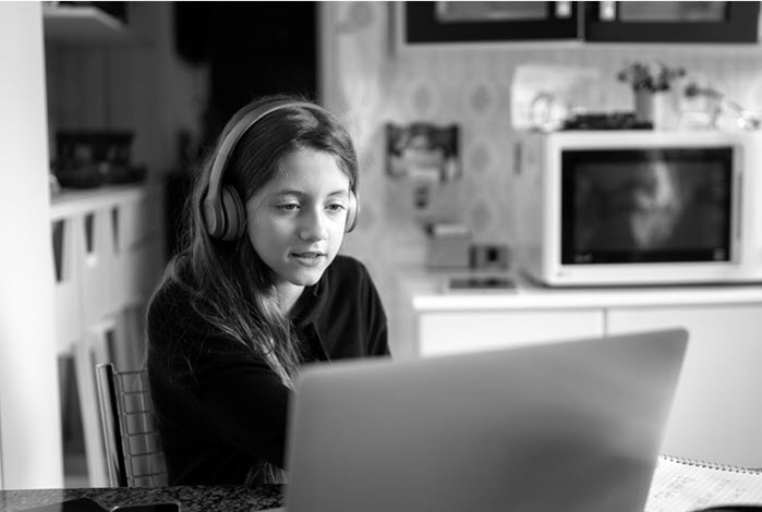 Girl with headphones looking at laptop and sitting at dining room table