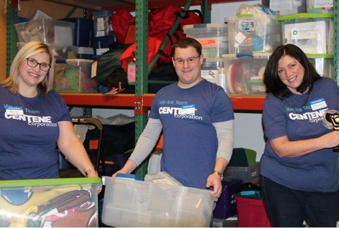 Centene employees volunteer by carrying bins of donated items