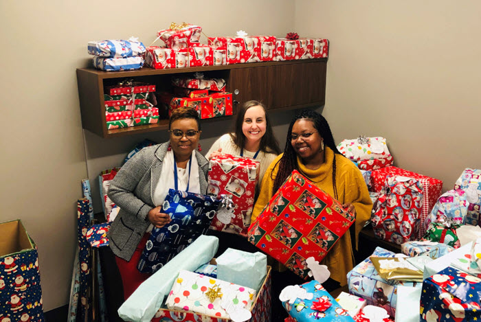 Centene employees pose with wrapped holiday gifts for donation