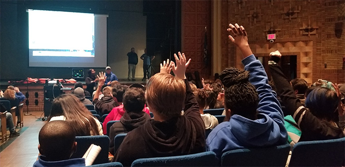 kids raise hands during social isolation presentation