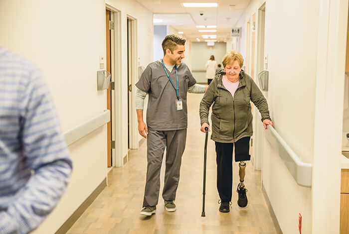physician walking member down hospital hall