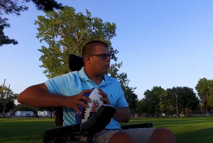 man in wheelchair holds football
