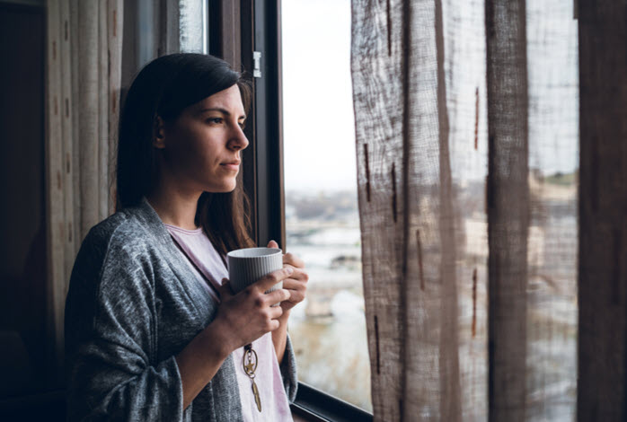 woman holding a coffee mug and staring through a window