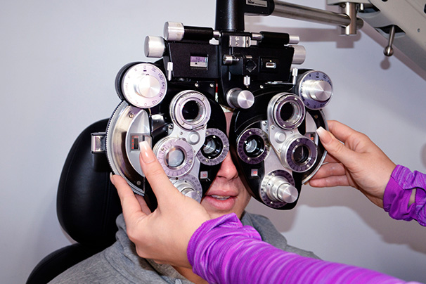 person having his vision measured by optometrist