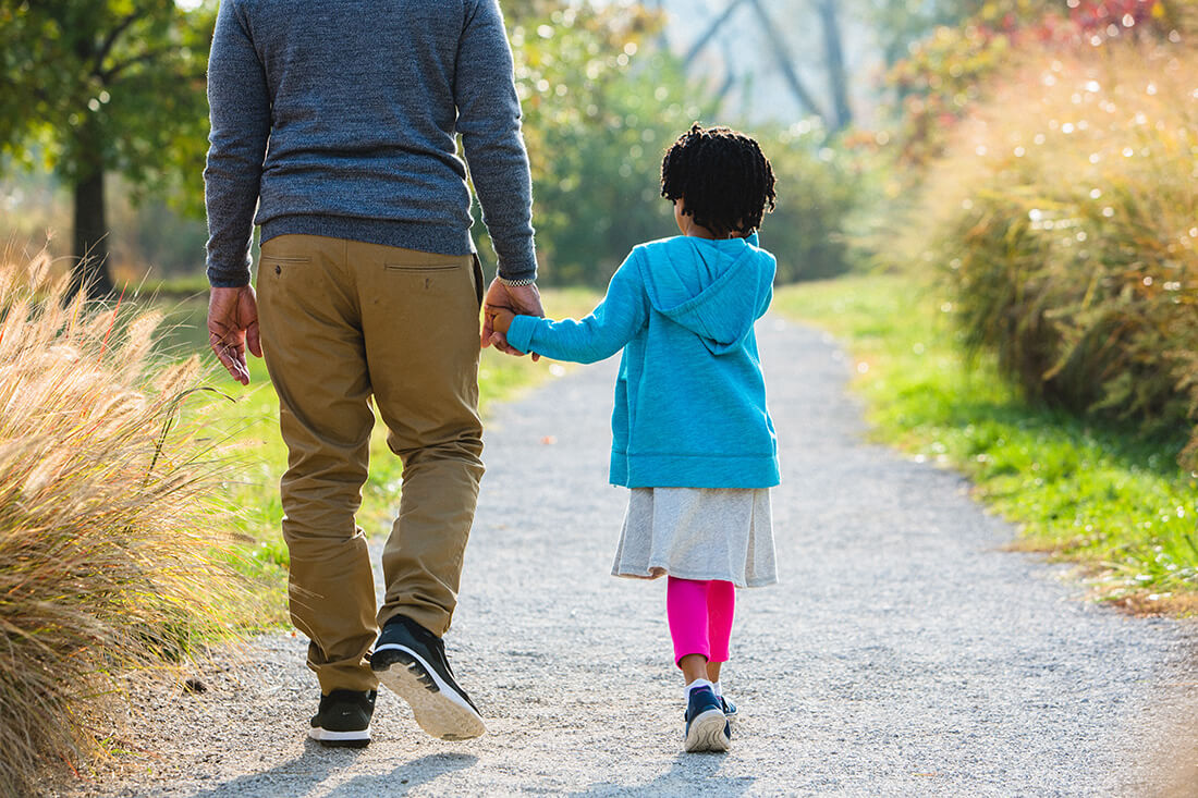 Grandfather and granddaughter walk together in park.