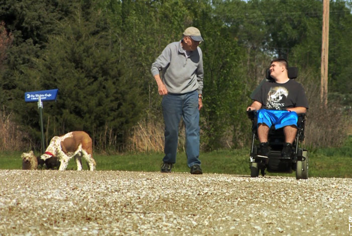 teenager in a wheelchair and grandfather walking a dog