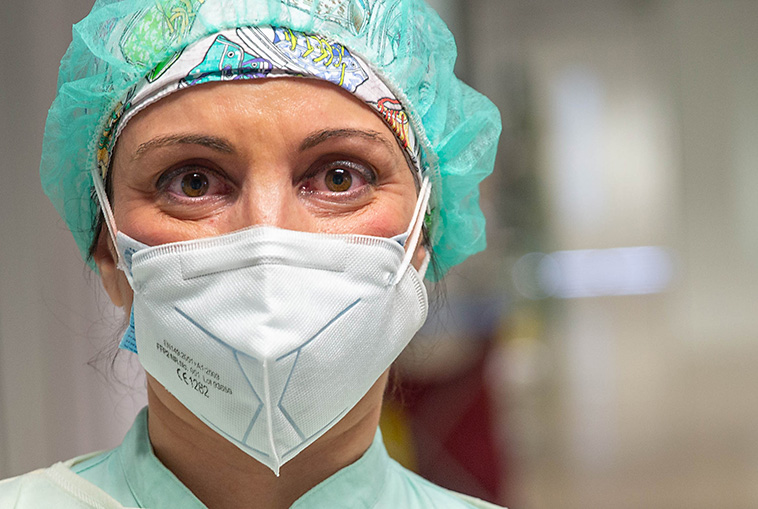 masked nurse in PPE looking straight at camera