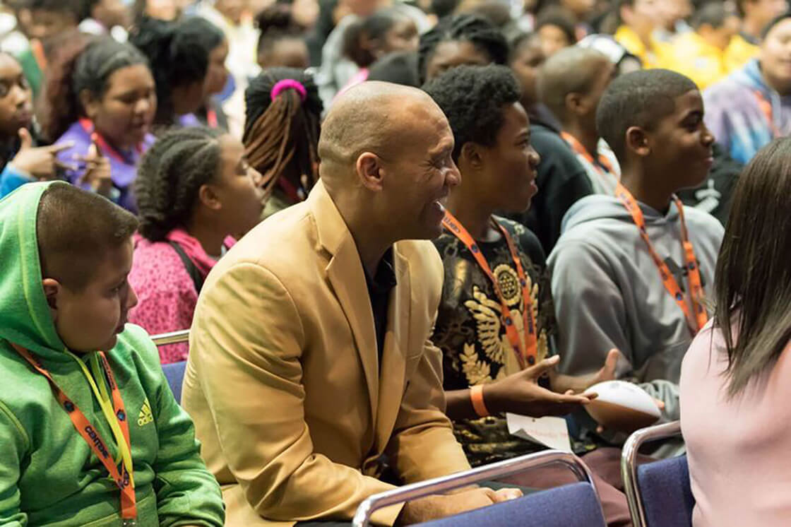 Aeneas Williams sits in a crowd of teenagers during Strong Youth Strong Communities summit